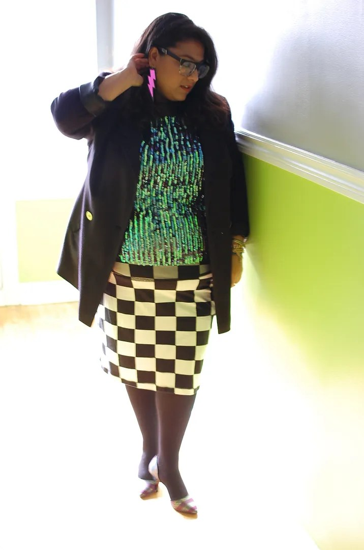 plus size outfit with blue aqua sequin top, black blazer, pink lightning bolt earrings, and checkerboard print skirt