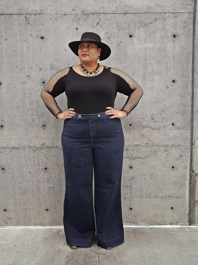 plus size outfit with wide-leg dark jeans and black mesh top