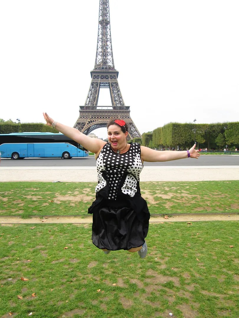 woman jumping in front of eiffel tower