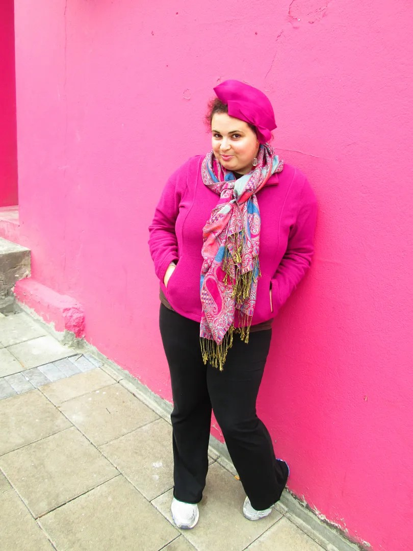 plus size outfit pink jacket, blue and pink scarf, pink hat, and black pants