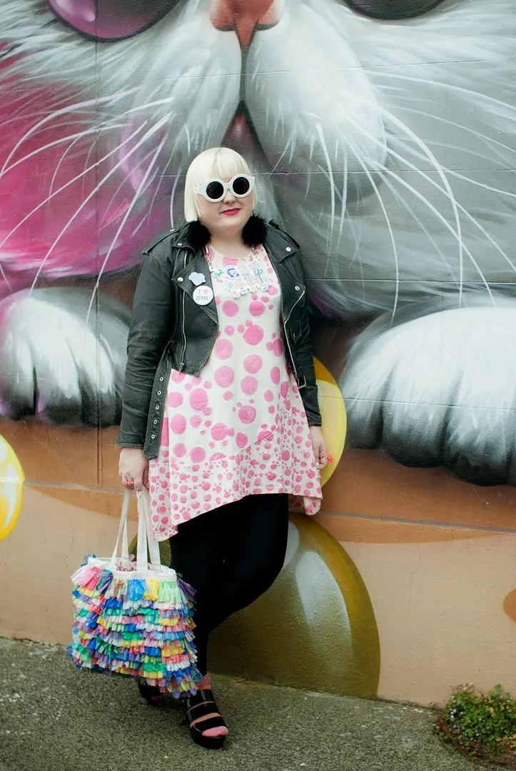 plus size outfit leather jacket and pink polka dot tunic with colorful bag