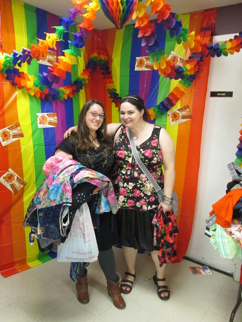 two women holding clothing in front of rainbow photobooth