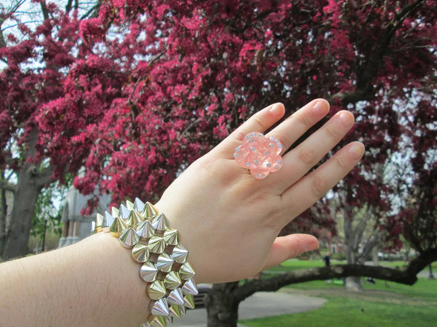 hand with pink rose statement ring and gold and silver spike bracelet in front of pink tree