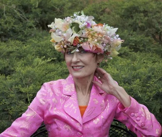 older woman wearing pink jacket and christian dior vintage floral hat