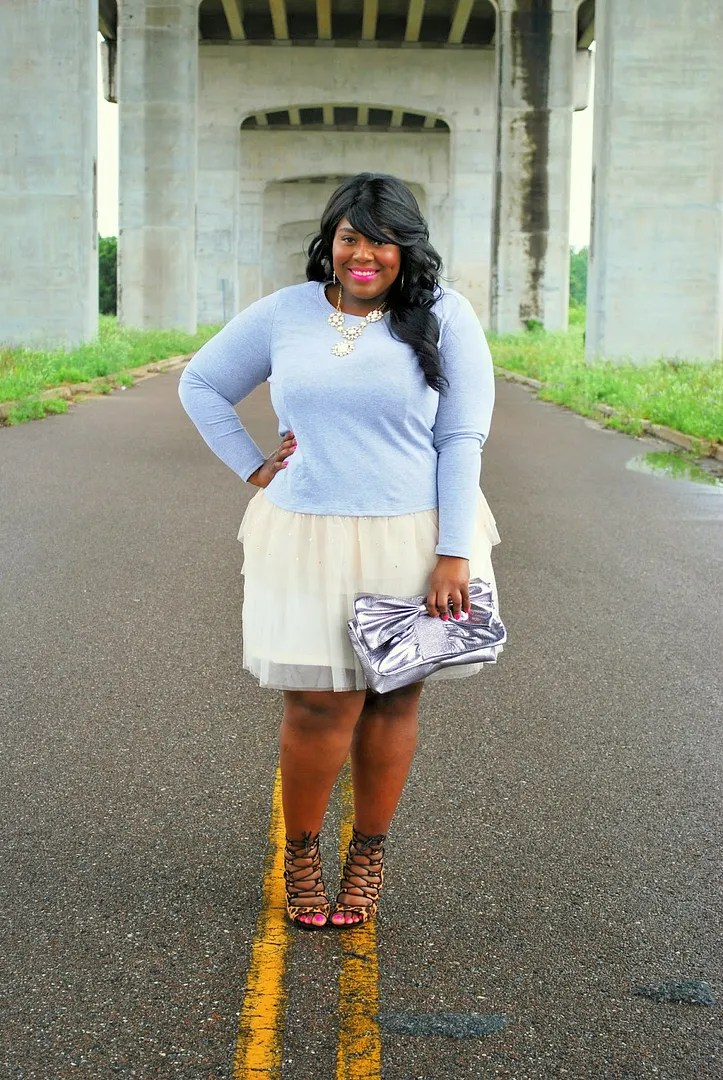 plus size outfit with cream tutu, blue-gray sweater, and silver bow clutch