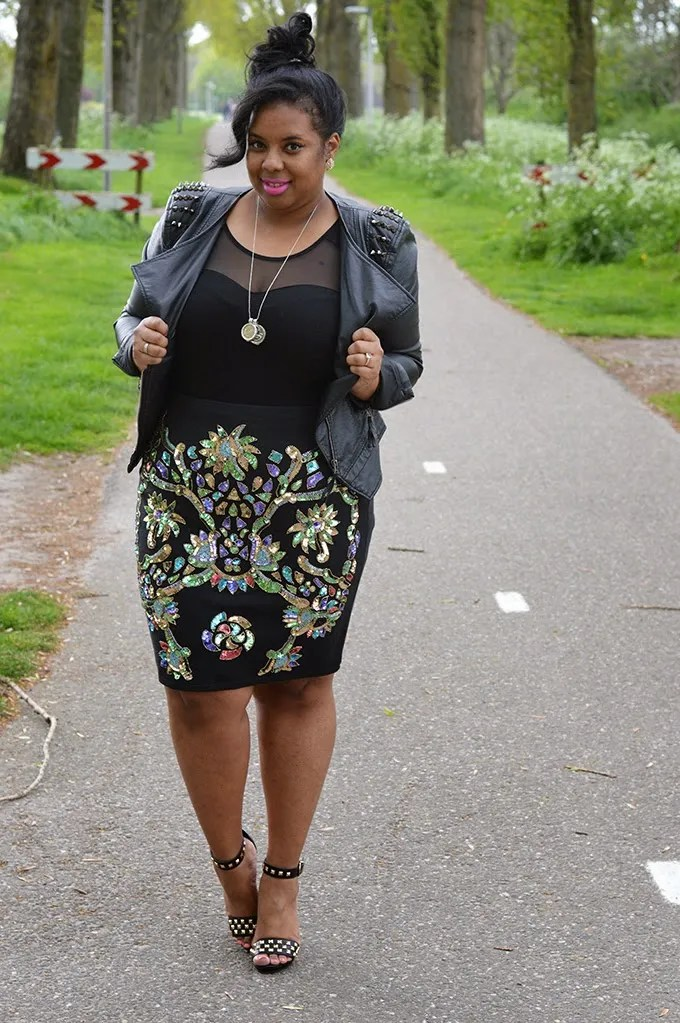 plus size outfit with black sheer top, leather jacket, and black and multicolored sequin skirt