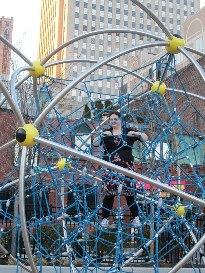 climbing on a blue and yellow rope structure on a playground