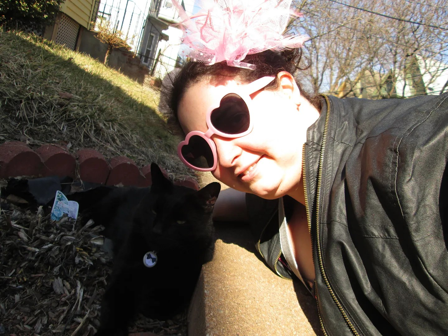 selfie of woman in leather jacket with pink sunglasses and black cat looking evil