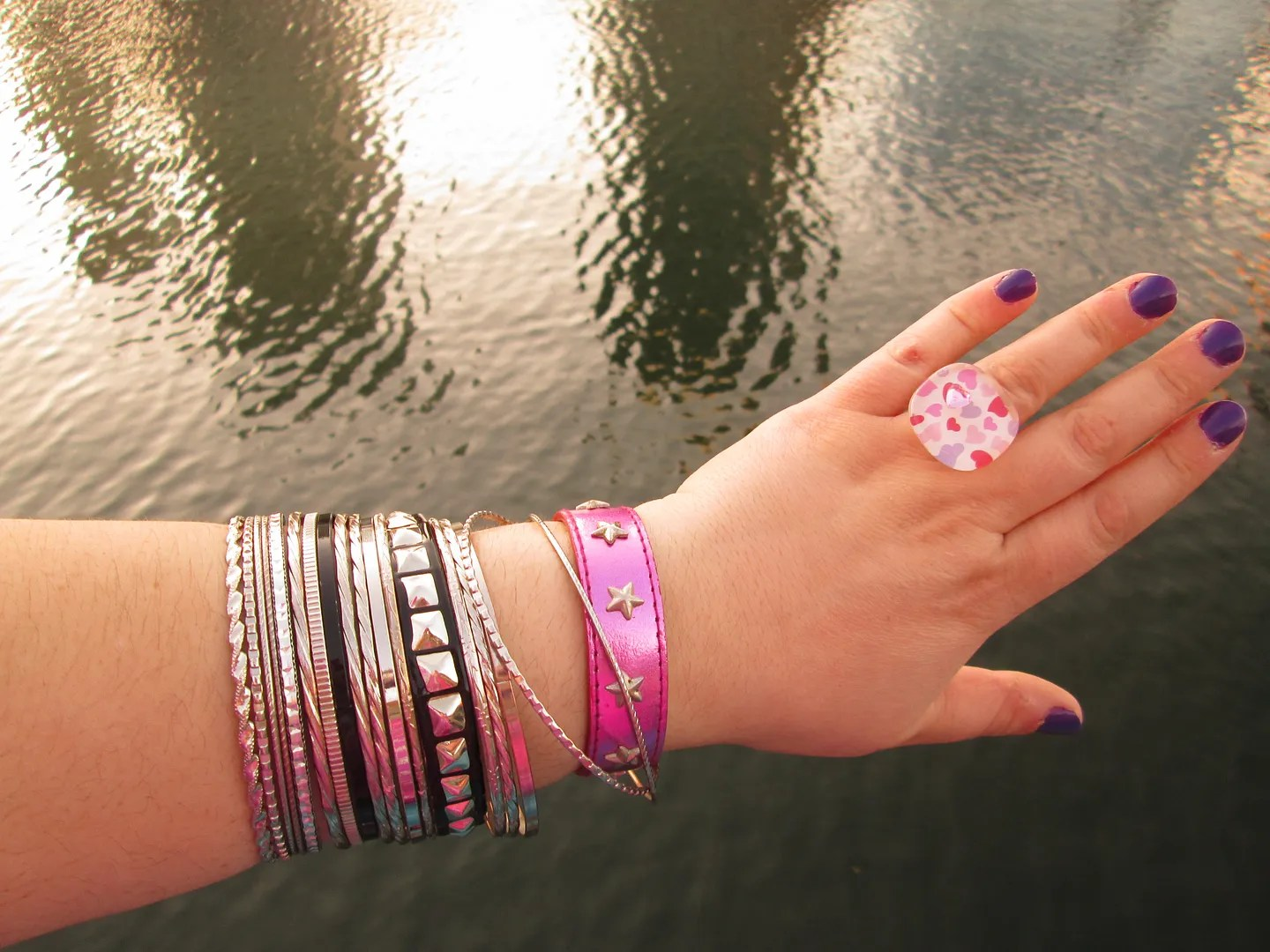 hand with purple nail polish, black and silver bangles, pink heart lucite ring, and pink metallic wristband with star studs
