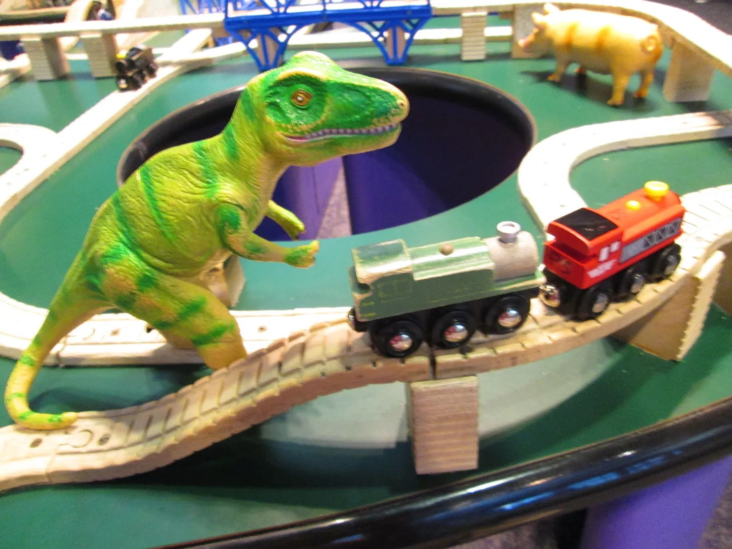 plastic dinosaur menacing wooden trains