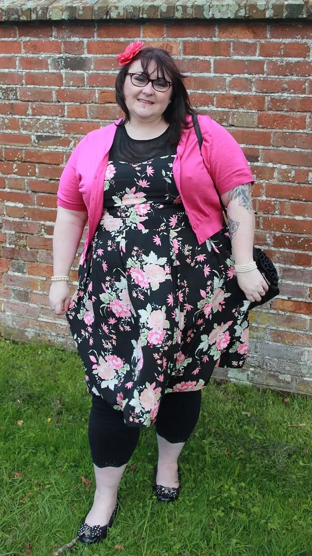 plus size outfit with black and pink floral dress, black leggings, and pink bolero