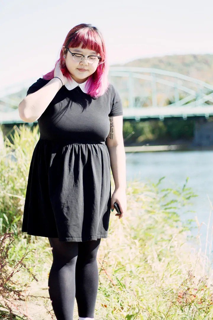 plus size woman with pink hair wearing black babydoll dress with white collar
