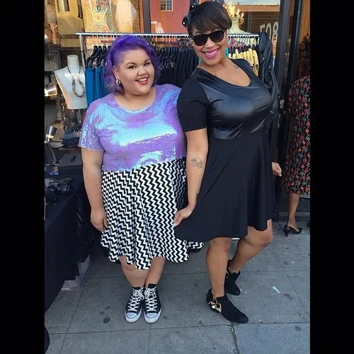 ashley nell tipton with purple hair and a purple iridescent shirt, with model wearing black leather skater dress
