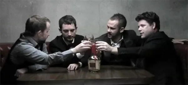 The actors who played the Hobbits in the LOTR movies sharing a drink in a booth