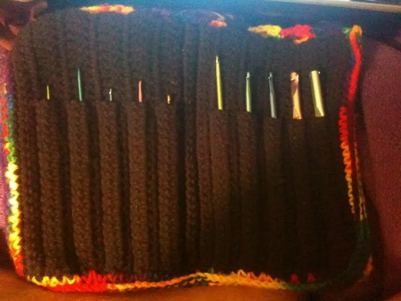crochet hook case, viewed from inside, black on inside with rainbow edging, 10 hooks in the case