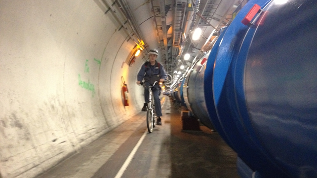 A worker cycles through the Large Hadron Collider tunnel