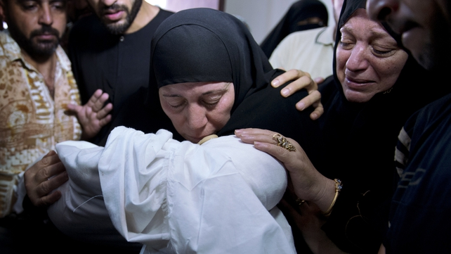 Relatives of Mohammed Deif's infant son hold his body ahead of his funeral