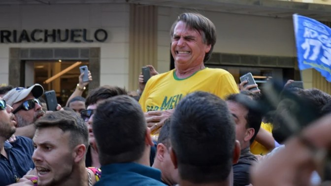 Jair Bolsonaro reacts after being stabbed in the stomach during a campaign rally