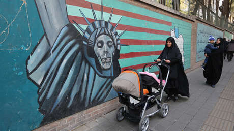 Women pass a mural against the United States during a protest in Tehran, Iran, on November 4, 2018.