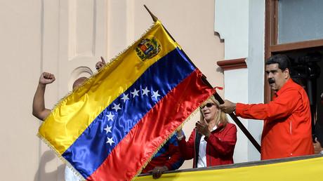 Venezuelas Präsident Nicolás Maduro (r.), flankiert von seiner Frau Cilia Flores (M.), hält eine venezolanische Flagge, während er von einem Balkon des Präsidentenpalastes Miraflores spricht.