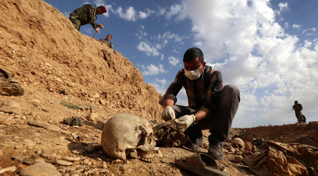 An Iraqi man inspects the remains of members of the Yazidi minority killed by the Islamic State (IS) jihadist group, February 3, 2015. © Safin Hamed
