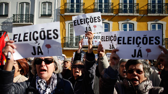 Demonstrators shout slogans and display posters calling for snap elections as they protest in front of the parliament during the vote of the 2014 State Budget in downtown Lisbon on November 26, 2013.(AFP Photo / Pedro Nunes)