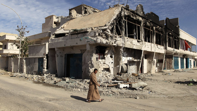 A man walks past a house which was destroyed during fighting between pro and anti-Gaddafi fighters in Sirt November 19, 2011. (Reuters/Mohammed Salem)