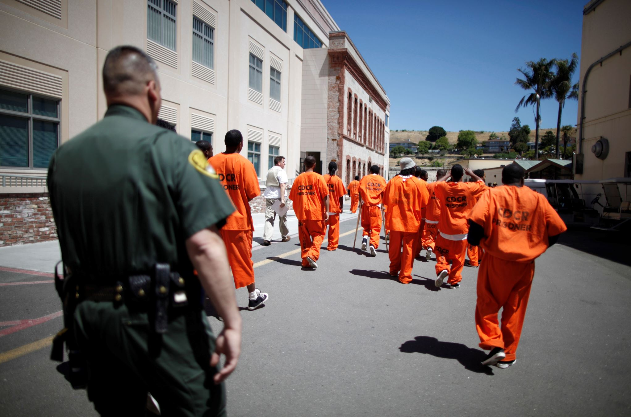 Inmates are escorted by a guard through San Quentin state prison in San Quentin, Calif.