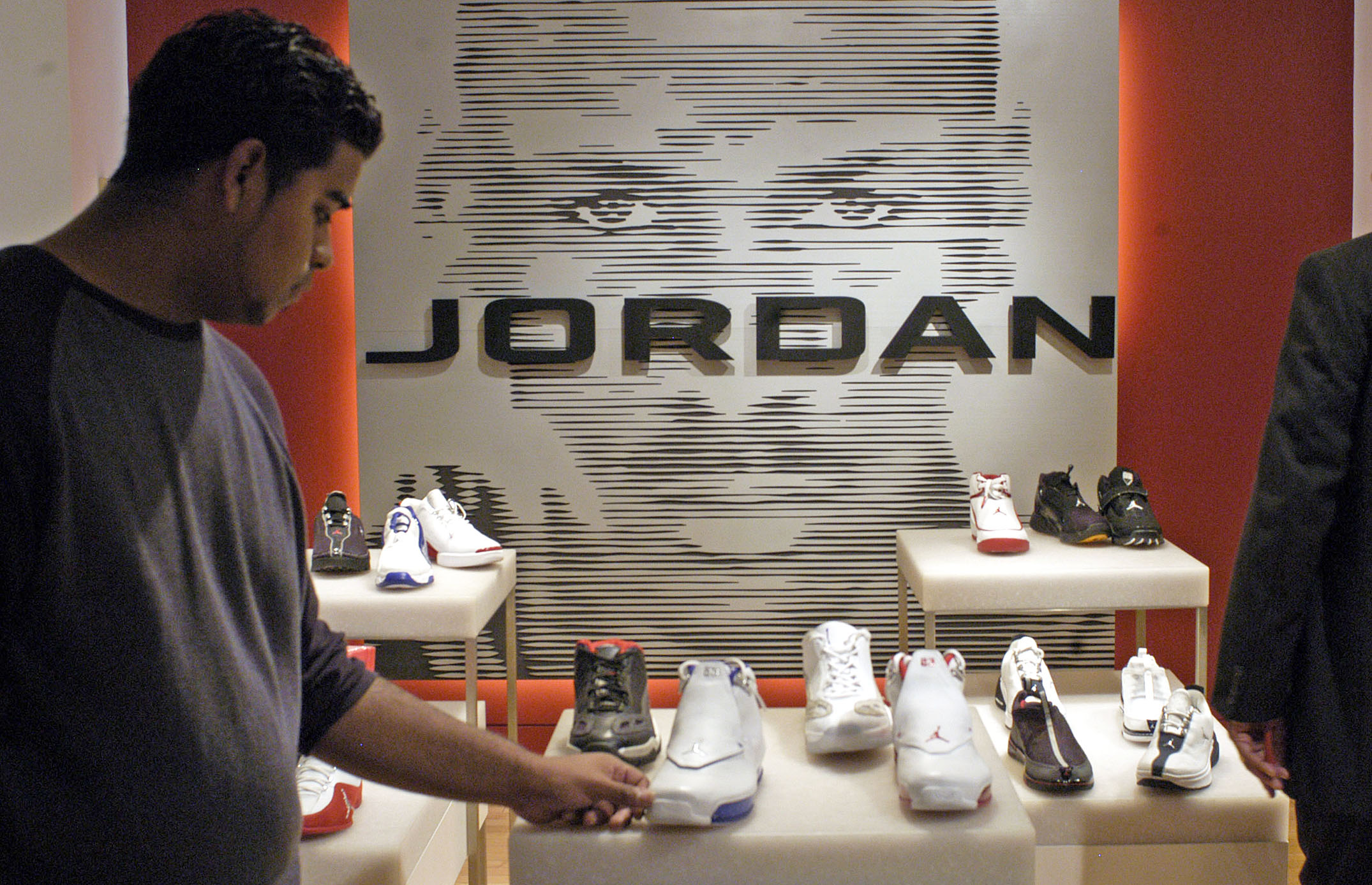 A man looks over Nike's Jordan line of athletic shoes at Niketown in New York.