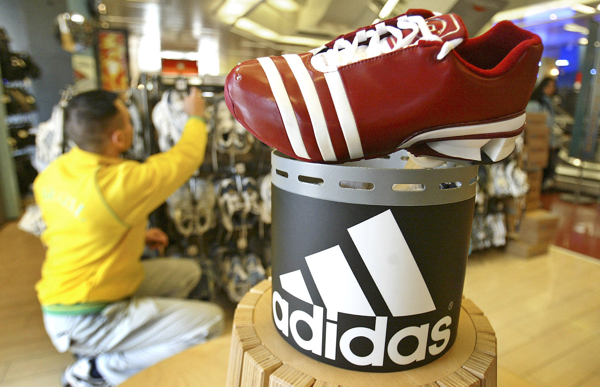 An employee arranges Adidas sports shoes on display in a sporting goods store.
