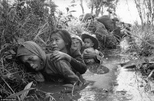 越南战争,西贡以西20英里的Bao Trai,妇女和儿童蹲在泥泞的运河中掩护。(Horst Faas/AP)