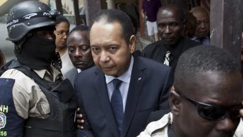 Jean-Claude Duvalier escorté par des policiers.