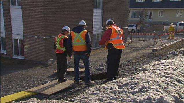 Des employés municipaux observent le cratère devant l'immeuble.