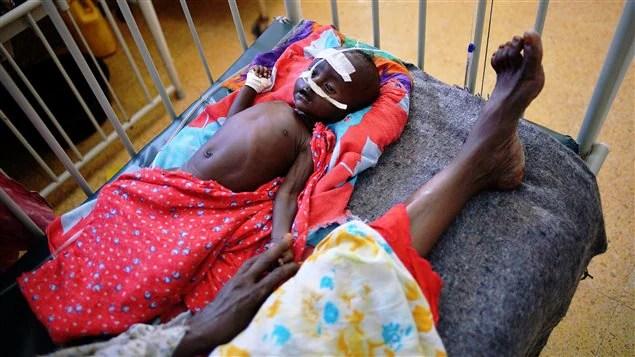 Un bébé somalien tient la main de sa mère dans un dispensaire.