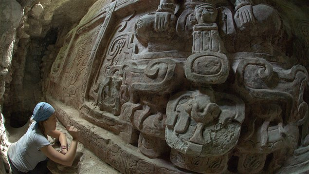 Une archéologue nettoie la frise maya découverte en juillet.