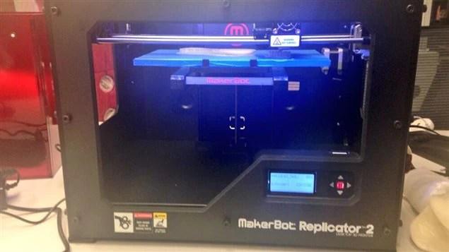 L'imprimante 3D, vue de face. La plaque bleue sert de base pour la «création». Elle bouge de haut en bas.