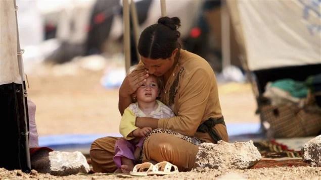 Une femme de la minorité yézidie console son enfant dans un camp de réfugiés de Qamishli, en Syrie.