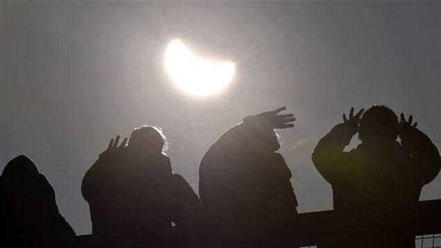 Des gens regardent une éclipse solaire.