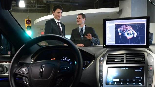 Le directeur de l'ingénierie chez Blackberry QNX, Sheridan Ethier, discutant avec le premier ministre du Canada, Justin Trudeau lors de sa visite des installation de Blackberry QNX à Ottawa lundi le 19 décembre 2016.