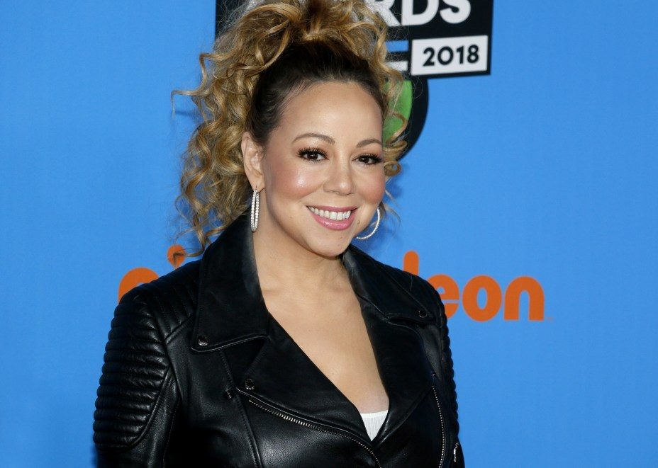 Mariah Carey looks elegant at a Nickelodeon event, rocking a black leather jacket with a smile on her face.