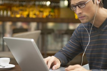 Man sitting at cafe table using laptop and wearing earphones