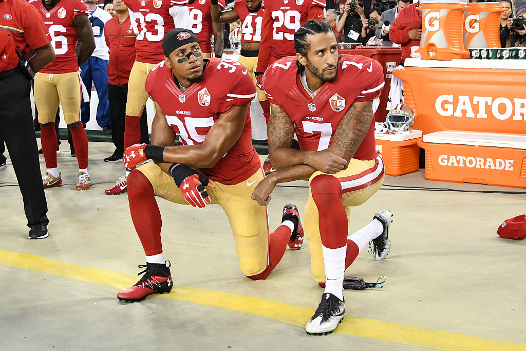 Colin Kaepernick and Eric Reid kneel in protest during the National Anthem in this September 12, 2016 file photo. (Photo by Thearon W. Henderson/Getty Images)