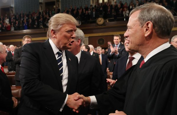 President Donald Trump (L) shakes hands with Chief Justice John Roberts (R) in the House chamber of the U.S. Capitol