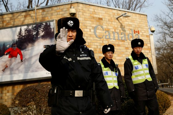 police officer gestures to photographer outside canadian embassy in China