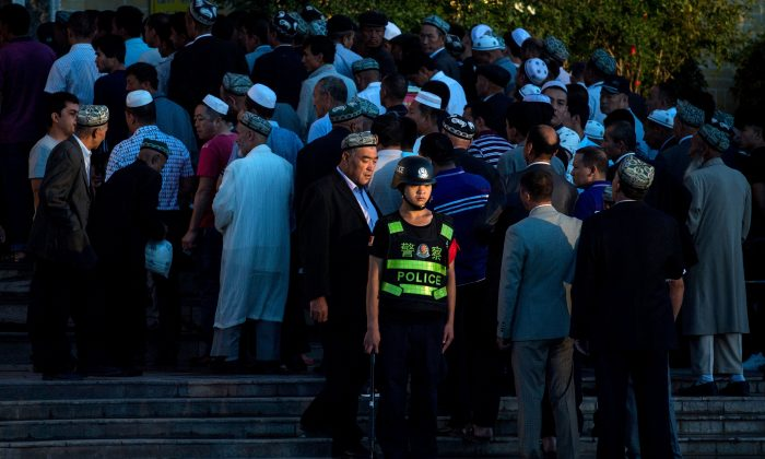 A policeman standing guard as Muslims arrive for the Eid al-Fitr morning prayer at the Id Kah Mosque in Kashgar in Xinjiang, China, on June 26, 2017. (Johannes Eisele/AFP/Getty Images)