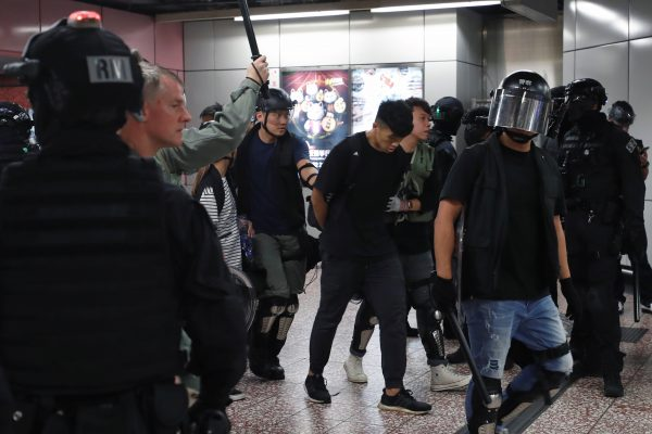 Riot police detain a man inside Prince Edward Mass Transit Railway (MTR) station after anti-extradition bill protest in Hong Kong