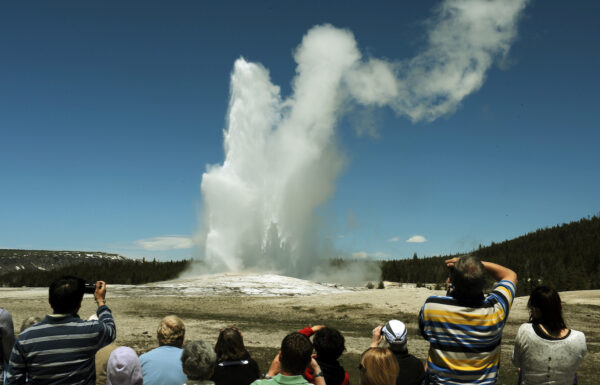 Tourists watch the 'Old Faithful' geyser