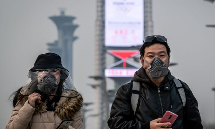 People wearing face masks walk at the Olympic park in Beijing on March 24, 2020. (Nicolas Asfouri/AFP via Getty Images)