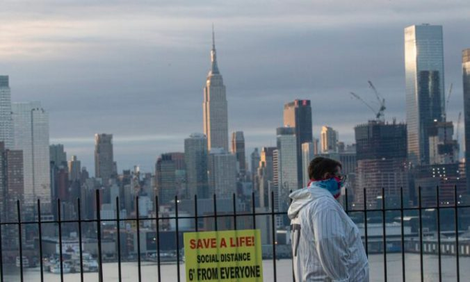 A man covers his face as the sun rises behind in Manhattan as seen from Weehawken, New Jersey on April 6, 2020. (Kena Betancur/Getty Images)