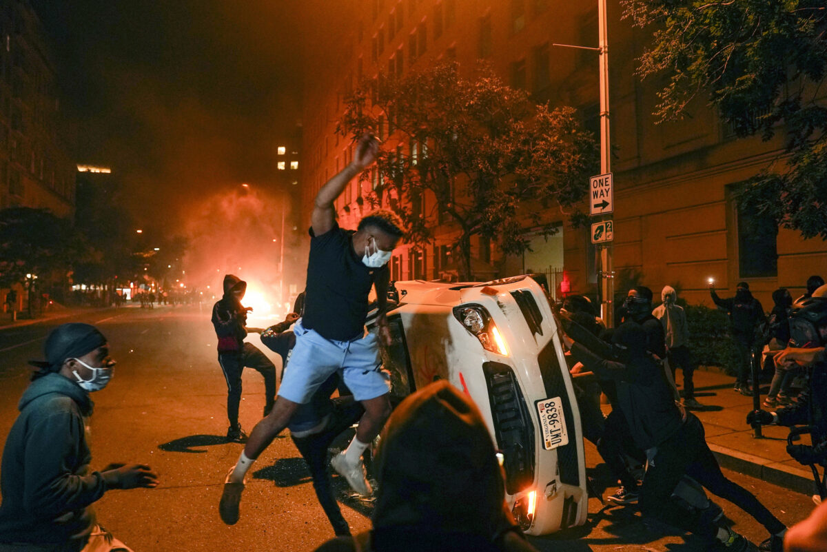 Demonstrators vandalize a car